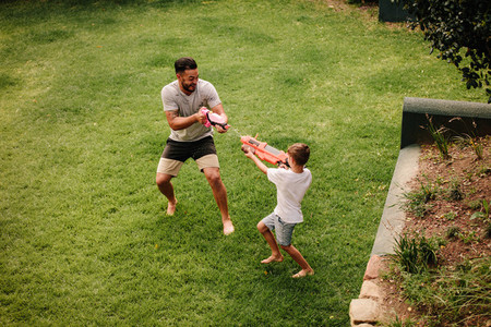 Father and son playing water gun fight outdoors