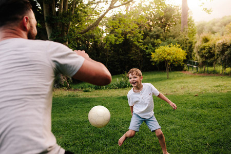 Father and son playing football in backyard garden