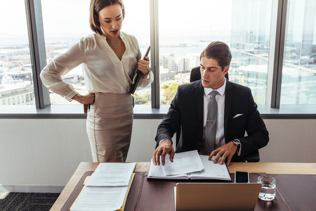 Business people discussing contract documents in office