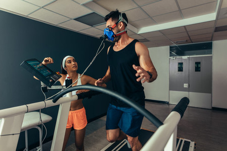 Woman monitoring runner with mask on treadmill