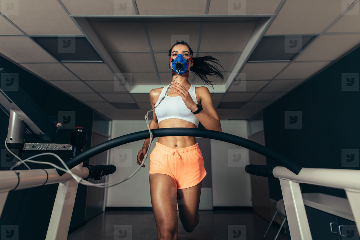 Fit woman running on treadmill with a mask