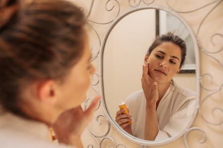 Female applying cream onto her face
