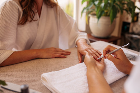 Nail technician giving customer a manicure at beauty salon
