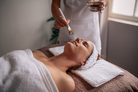 Woman getting facial mask at spa salon