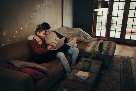 Couple relaxing with a laptop in cozy living room