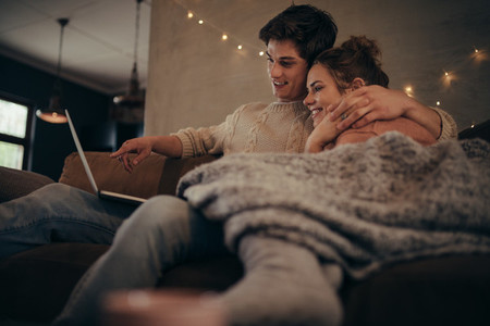 Love couple in hygge house with laptop