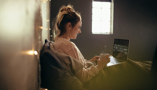 Woman on bed using laptop and having coffee