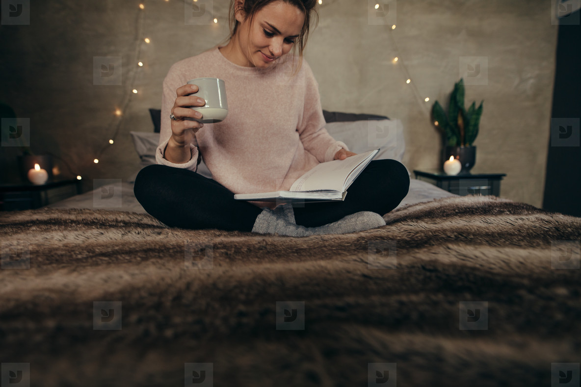 Relaxed woman on bed reading book with coffee