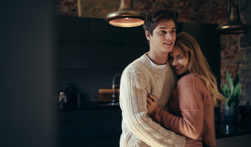 Man hugging his girlfriend at home