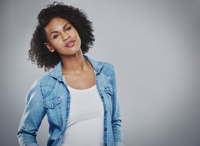 Happy woman with curly hair over gray background