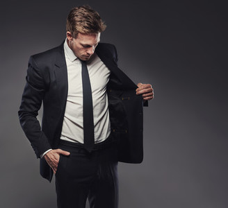 Young businessman in a stylish suit aganst a grey background