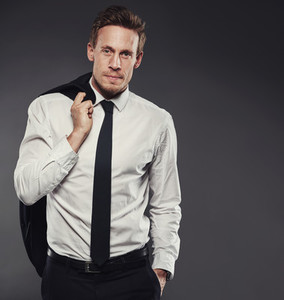 Confident and handsome young businessman standing against a grey background