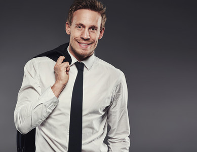 Stylish young businessman smiling and standing against a grey background
