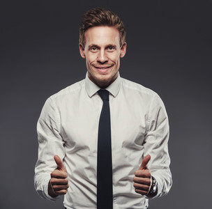 Enthusiastic businessman giving the thumbs up against a grey background