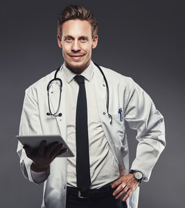 Smiling young doctor with a tablet against a grey background