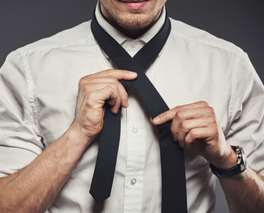 Young businessman tying his necktie for the business day
