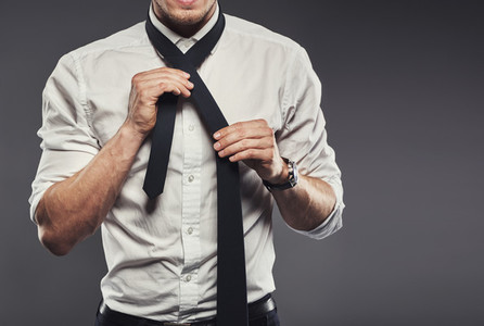 Businessman dressing tying his necktie
