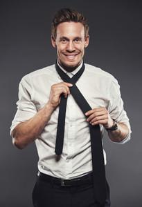 Smiling businessman tying his necktie
