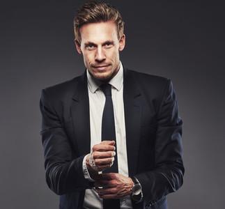 Pensive attractive businessman adjusting his cuff