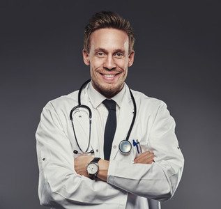 Young happy physician wearing medical white coat