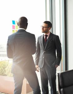 Serious young businessman talking to a colleague