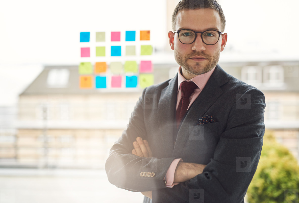 Serious young businessman with crossed arms
