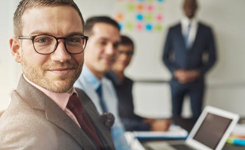 Cute man in eyeglasses with co workers in meeting