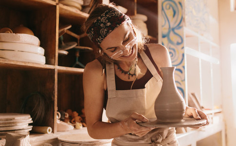 Woman holding a finished clay pot on potters wheel base