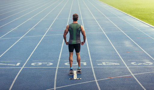 Sprinter standing on starting block on running track