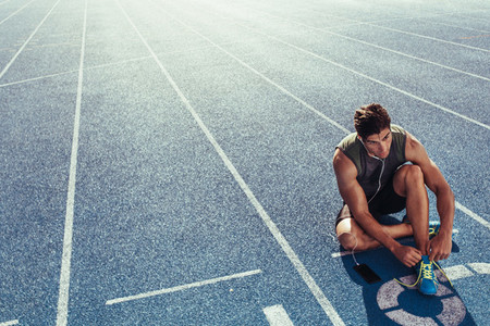 Sprinter tying shoe lace sitting on running track