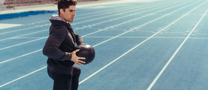 Athlete training with a medicine ball on running track