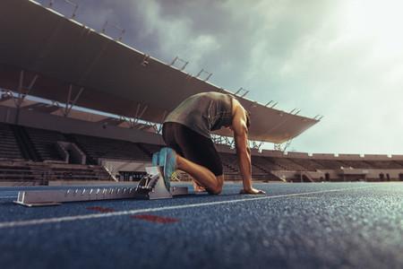 Sprinter resting his feet on a starting block on running track