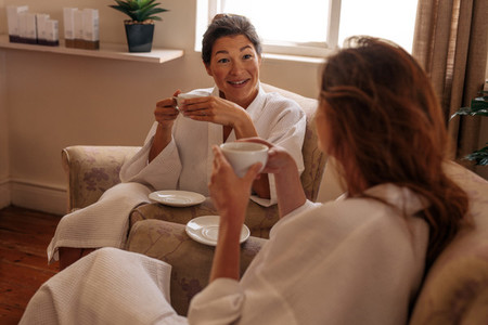 Female friends having herbal tea and chatting in spa