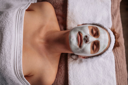 Woman with facial mask lying on spa table