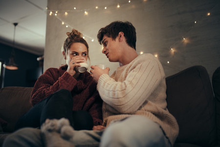 Couple relaxing on sofa having coffee