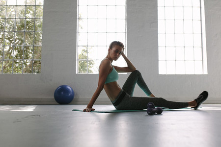 Healthy woman resting after training in gym