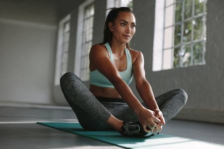 Woman doing yoga stretches in gym