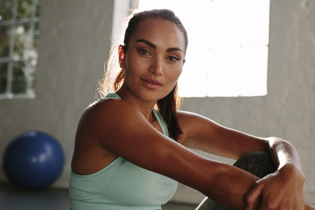 Fit woman relaxing after exercising at health club
