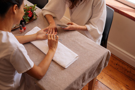 Beautician filing female clients nails at spa beauty salon