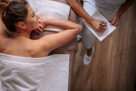 Woman lying on massage table with masseuse making notes