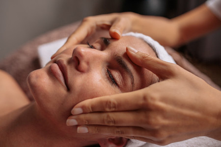 Beautiful woman relaxing with face massage at beauty spa