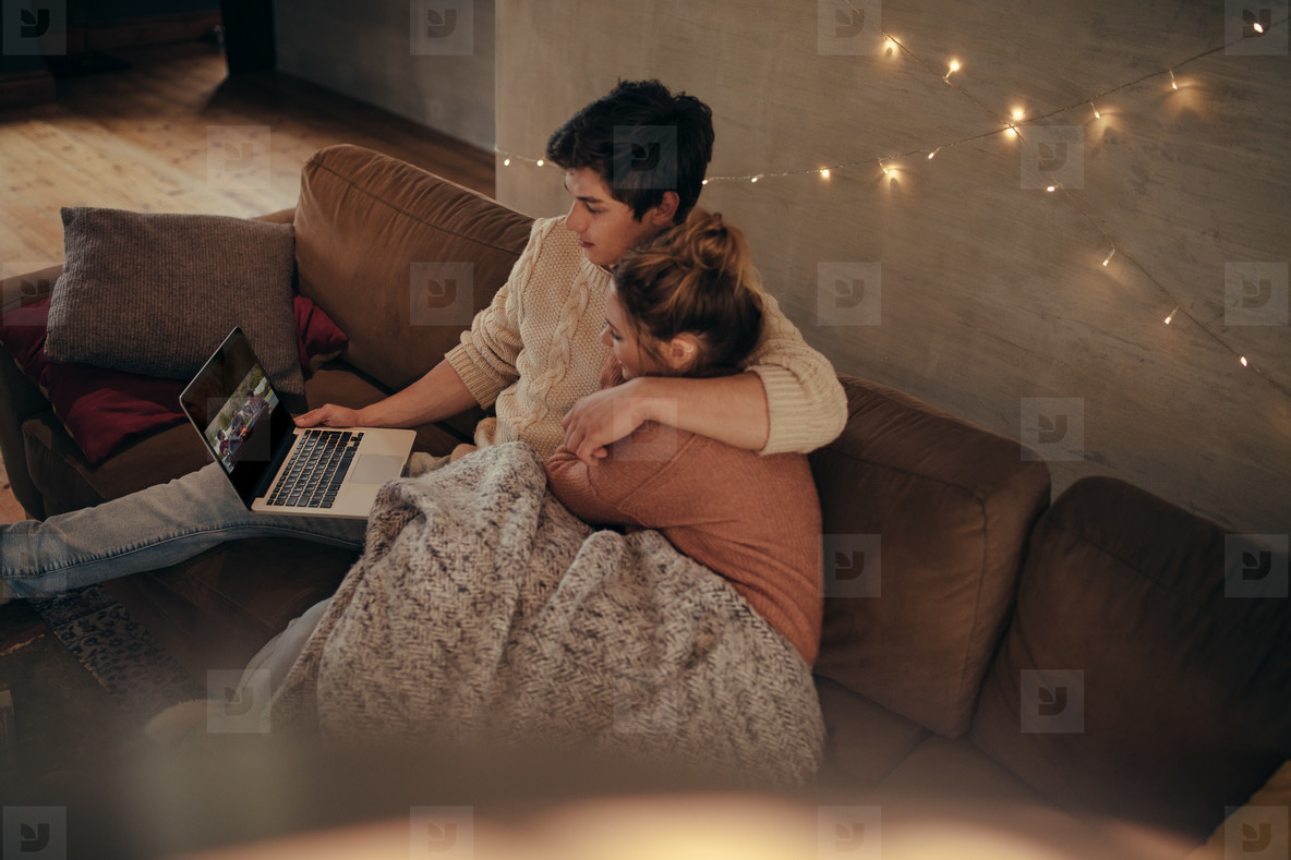 Cozy young couple sitting on sofa with laptop