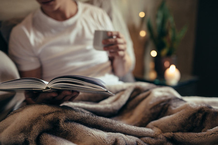 Man reading book on bed at home