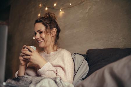 Cheerful woman drinking coffee in bedroom