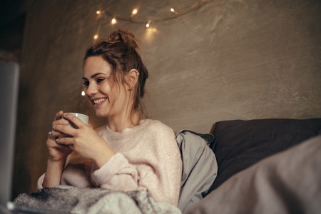 Cheerful woman drinking coffee in bedroom