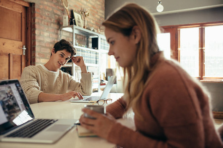 Man sitting at table and looking at his girlfriend