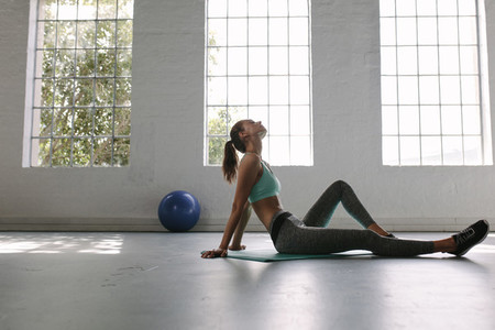 Tired woman taking rest after workout at gym
