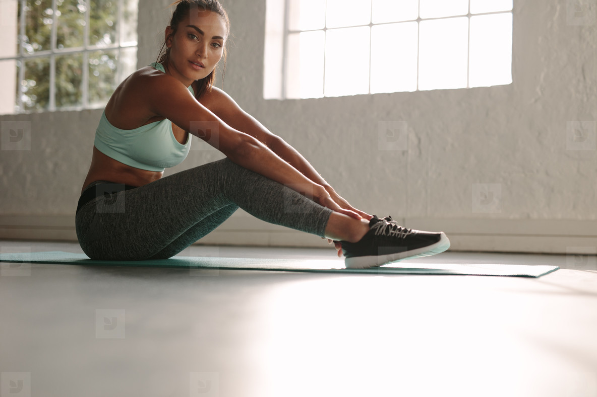 Healthy woman taking break after workout in gym