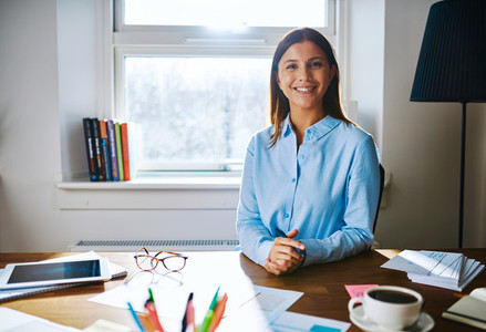 Confident smiling woman at desk