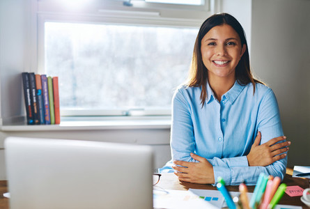 Confident grinning woman at desk behind laptop